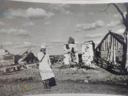 kobieta przy spalonych domach