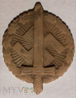 Miecz przed swastyką w okrągłym wieńcu liści dębu